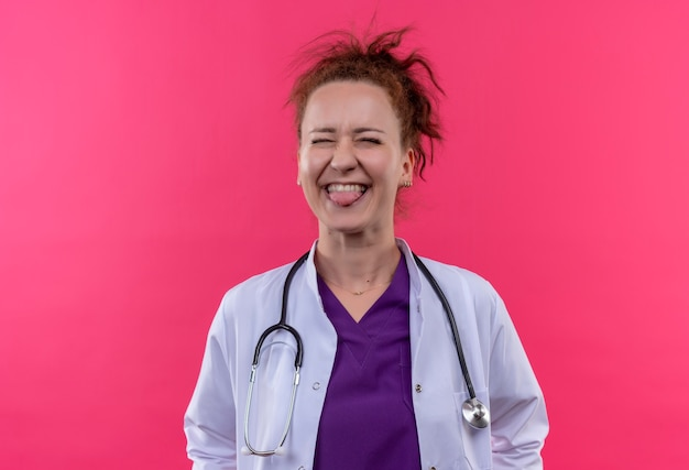 Junge ärztin, die weißen mantel mit glücklichem und aufgeregtem herausstehendem zunge des stethoskops trägt, das über rosa wand steht