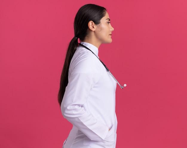 Junge ärztin im medizinischen mantel mit seitlich stehendem stethoskop mit sicherem ausdruck über rosa wand