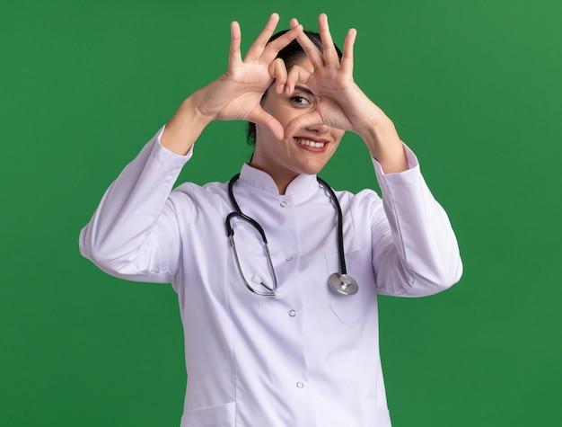Junge ärztin im medizinischen mantel mit stethoskop, das vorne mit lächeln auf gesicht schaut, das herzgeste mit den fingern macht, die über grüner wand stehen