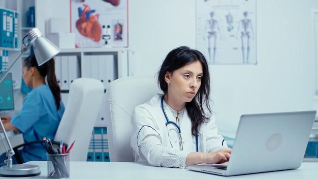 Junge ärztin im privaten medizinischen kabinett, die auf laptop schreibt, während die krankenschwester im hintergrund arbeitet. heilpraktiker im gesundheitswesen im krankenhaus und in der gesundheitsforschung