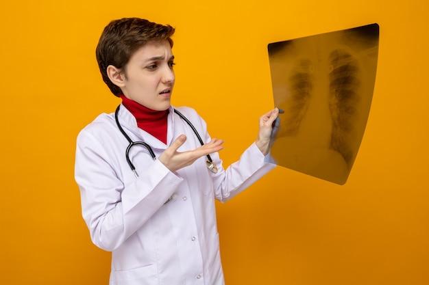 Junge ärztin im weißen kittel mit stethoskop, die röntgenaufnahme der lunge hält und mit dem arm darauf zeigt, dass sie verwirrt über der orangefarbenen wand steht?