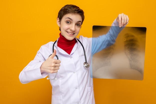 Junge ärztin im weißen kittel mit stethoskop, die röntgenaufnahme der lunge hält und selbstbewusst lächelt und daumen nach oben auf orange zeigt