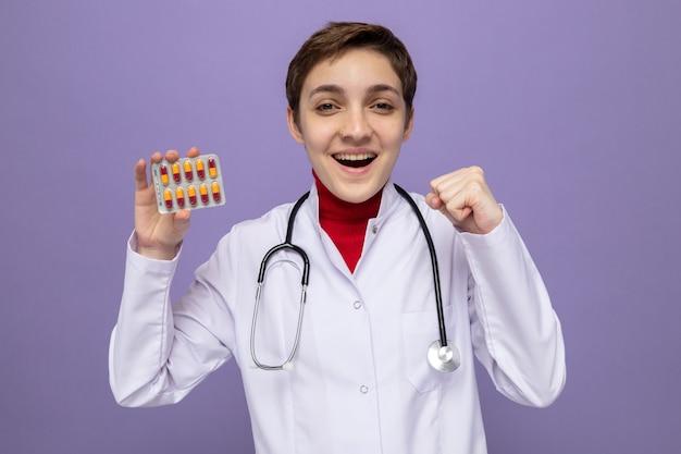 Junge ärztin im weißen kittel mit stethoskop um den hals, die blister mit pillen hält, glücklich und aufgeregt, die faust auf lila stehend