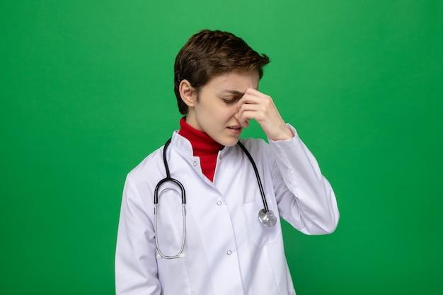 Junge ärztin im weißen kittel mit stethoskop um den hals, die unwohl müde und überarbeitet aussieht, indem sie ihre nase zwischen geschlossenen augen berührt, die auf grün stehen