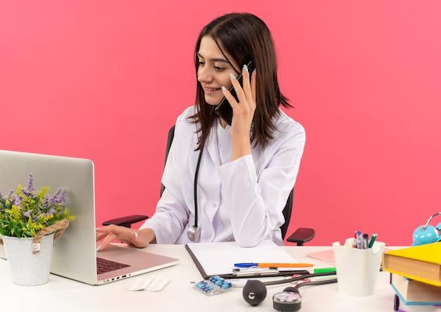 Junge ärztin im weißen kittel mit stethoskop um ihren hals, der am laptop arbeitet und auf handy mit lächeln auf gesicht sitzt, das am tisch über rosa wand sitzt