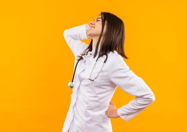 Junge ärztin im weißen kittel mit stethoskop um ihren hals, der unwohl aussieht und ihren rücken berührt, der schmerz fühlt, der über der orangefarbenen wand steht