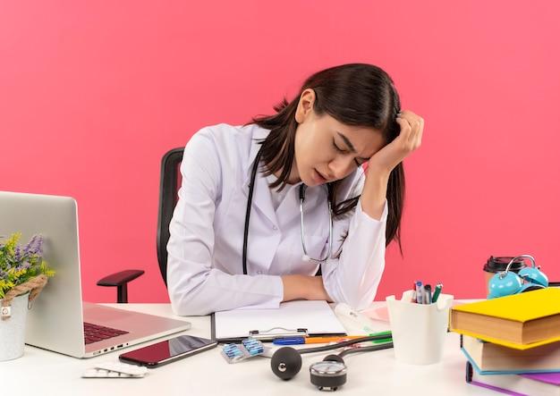Junge ärztin im weißen kittel mit stethoskop um ihren hals suchen reifen und überarbeitet sitzen am tisch mit laptop über rosa wand