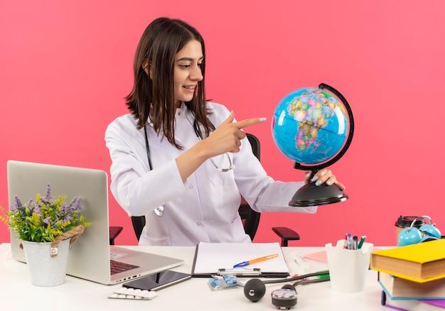 Junge ärztin im weißen mantel mit stethoskop um ihren hals, der globus hält, der mit lächeln auf gesicht sitzt, das am tisch mit laptop über rosa wand sitzt