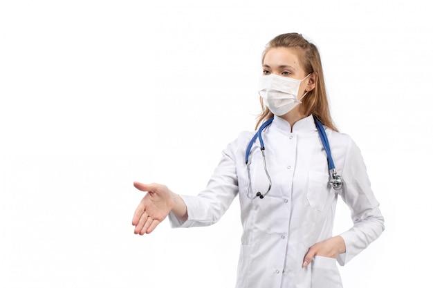 Junge ärztin im weißen medizinischen anzug im weißen schutzmaskenstethoskop händeschütteln auf dem weiß