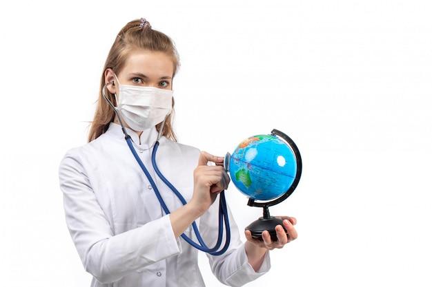 Junge ärztin im weißen medizinischen anzug in der weißen schutzmaske, die den kleinen globus durch stethoskop auf dem weiß hört