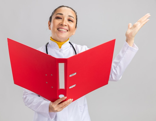 Junge ärztin im weißen medizinischen kittel mit stethoskop um den hals, die einen roten ordner glücklich und aufgeregt hält