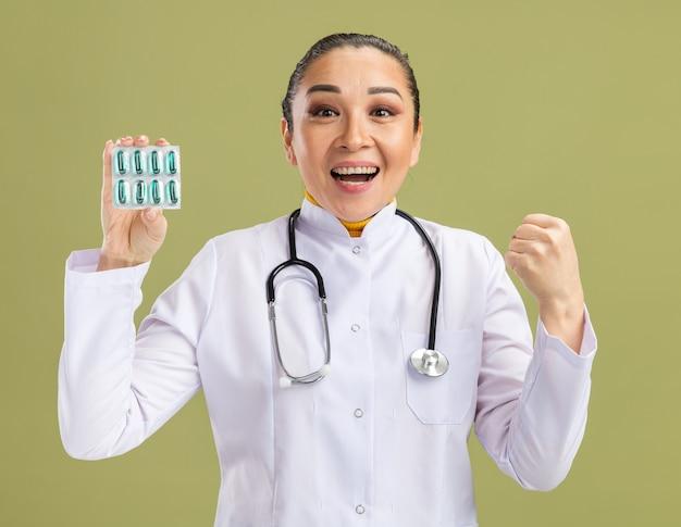 Junge ärztin im weißen medizinmantel mit stethoskop um den hals, die blase mit pillen hält, die die faust glücklich und aufgeregt über grüner wand zusammenballen