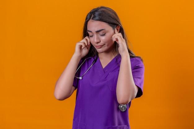 Junge ärztin in der medizinischen uniform mit phonendoskop, das mit geschlossenen augen steht und sich gestuft fühlt, das starke kopfschmerzen über lokalisiertem orangefarbenem hintergrund hat