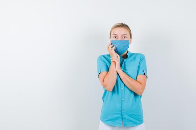 Junge ärztin in medizinischer uniform, maske, die hand auf wange hält und verängstigt aussieht looking