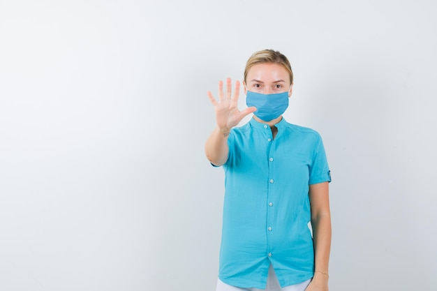 Junge ärztin in medizinischer uniform, maske mit stoppgeste und ernstem blick