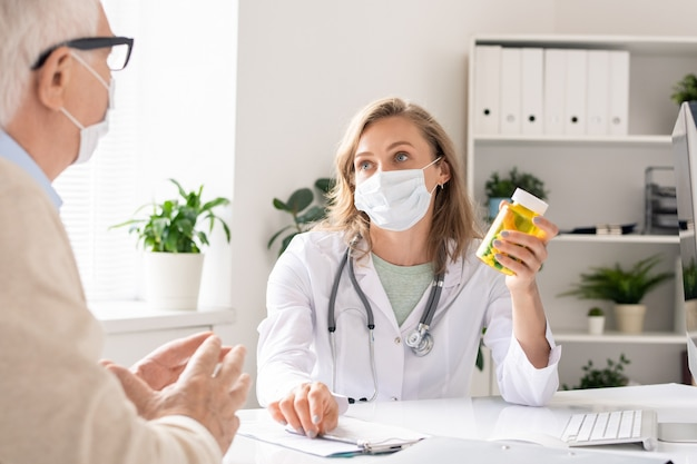 Junge ärztin in schutzmaske, die flasche mit pillen hält, während sie zeigt und dem patienten im krankenhaus empfiehlt