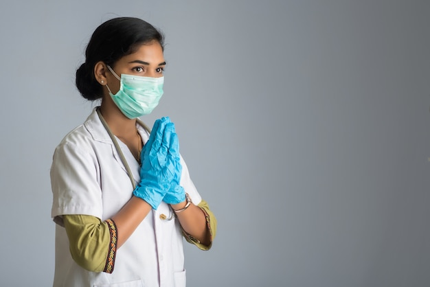 Junge ärztin macht namaste wegen ausbruch von covid-19. neue begrüßung, um die ausbreitung von coronavirus zu vermeiden, anstatt mit einer umarmung oder einem händedruck zu begrüßen.