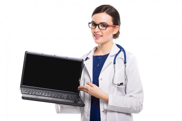Junge ärztin mit dem stethoskop, das laptop in ihren händen in der weißen uniform hält
