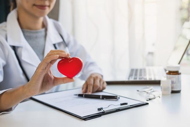 Junge ärztin mit dem stethoskop, das rotes herz hält, kardiologisches gesundes pflegekonzept