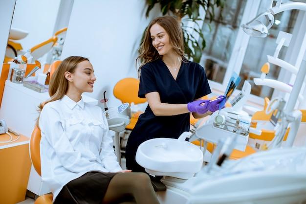 Junge ärztin mit schutzhandschuhen röntgenbild mit ihrem patienten im zahnarztbüro überprüfend