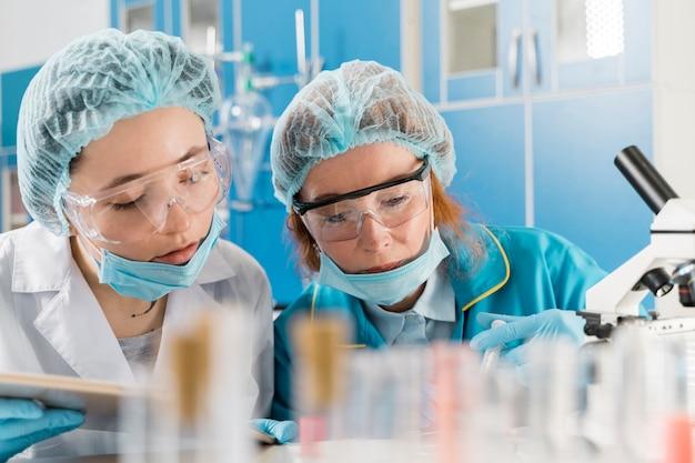 Junge ärztinnen, die an einem impfstoff arbeiten