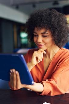 Junge afrikanerin, die mit technologie arbeitet