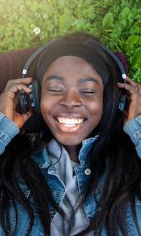 Junge afrikanerin, die musik liegt im park hört.