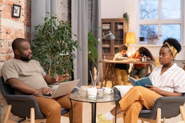 Junge afrikanerin mit offenem buch und ihr mann mit laptop sitzen in grauen sesseln und interagieren, während ihre kinder hausaufgaben machen