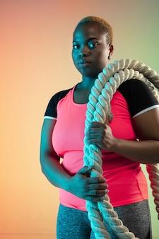 Junge afrikanische amerikaner plus größe weibliche modelle, die auf gradientenwand trainieren