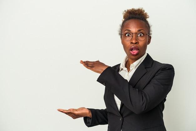 Junge afrikanische amerikanische frau des geschäfts lokalisiert auf weißem hintergrund schockiert und überrascht, einen kopienraum zwischen den händen zu halten.