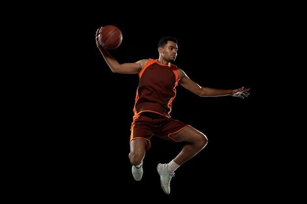 Junge afrikanische basketballspieler, die auf schwarzem studiohintergrund trainieren.