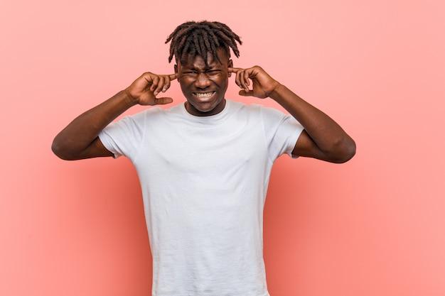 Junge afrikanische bedeckungsohren des schwarzen mannes mit seinen händen.