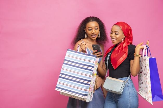 Junge afrikanische damen, die etwas auf einem handy ansehen, während sie einkaufstüten tragen