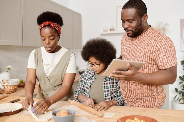 Junge afrikanische dreiköpfige familie, die hausgemachtes gebäck kocht