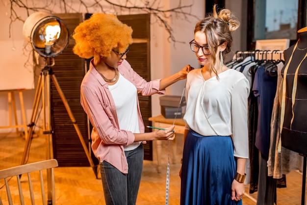 Junge afrikanische ethnische frau, die messungen eines weiblichen kunden im schneideratelier vornimmt