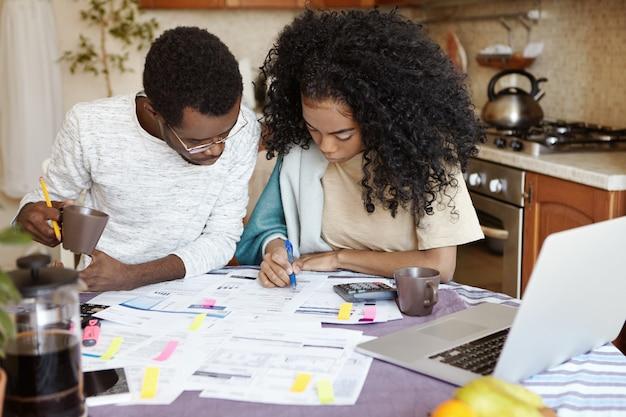 Junge afrikanische familie mit schuldenproblemen, die nicht in der lage ist, für gas und strom zu bezahlen, finanzen zu verwalten, mit papieren am küchentisch zu sitzen, rechnungen zu berechnen und zu versuchen, ihre haushaltskosten zu senken