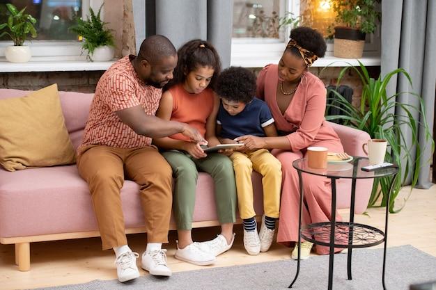 Junge afrikanische familie von vater, mutter, sohn und tochter mit tablet, die auf der couch gegen das fenster im wohnzimmer sitzt und einen film sieht