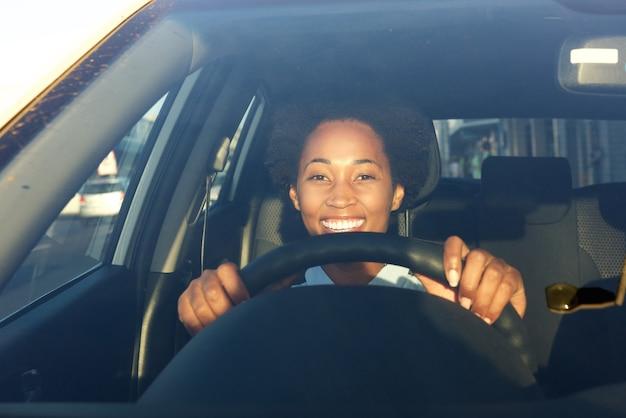 Junge afrikanische frau, die ein auto und ein lächeln antreibt
