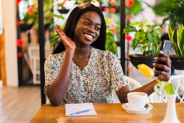 Junge afrikanische frau, die ein selfie im kaffeegeschäft nimmt