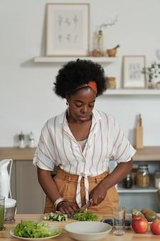 Junge afrikanische frau, die gemüse für vegetarischen salat schneidet