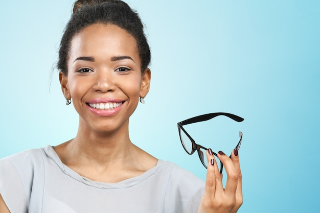 Junge afrikanische frau, die ihre brillen hält