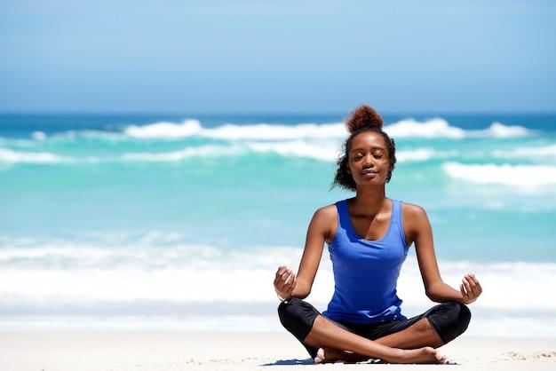 Junge afrikanische frau, die in der yogahaltung am strand meditiert