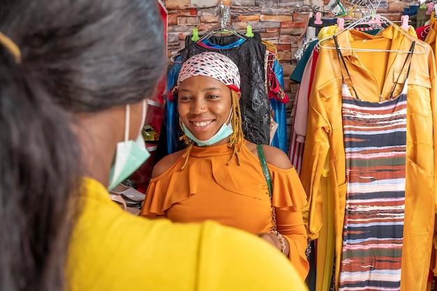 Junge afrikanische frau, die in einem lokalen boutique-laden einkaufen, lächelt und mit jemandem spricht