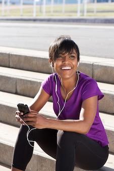 Junge afrikanische frau, die mit handy und kopfhörern sich entspannt