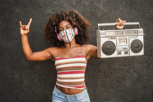 Junge afrikanische frau, die musik in der vintage-stereoanlage der boombox hört - fokus auf gesicht