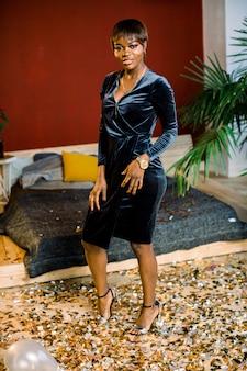 Junge afrikanische frau, die neues jahr oder ein ereignis feiert, aufgeregt und glücklich, im stilvollen raum mit konfetti auf dem boden stehend.