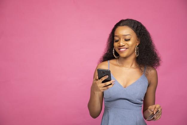 Junge afrikanische frau, die online mit ihrem smartphone einkauft