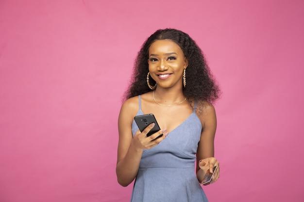 Junge afrikanische frau, die online mit ihrem smartphone und einer kreditkarte kauft