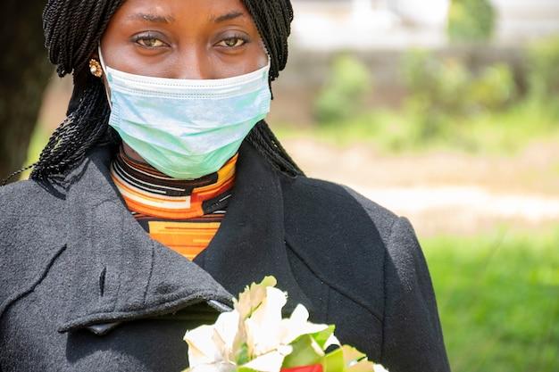Junge afrikanische frau, die trauert, schwarz trägt und blumen hält