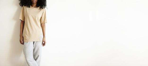 Junge afrikanische frau gekleidet in losem t-shirt und grauer baumwollhose, die mit gekreuzten beinen gegen weiße leere wand stehen. stilvolle dunkelhäutige studentin, die sich drinnen ausruht